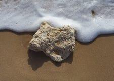 Pietra nella sabbia ed in un'onda Immagini Stock Libere da Diritti