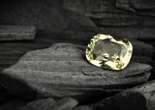 Pietra preziosa gialla sfaccettata dei gioielli sul fondo del darck Immagine Stock
