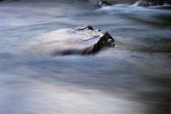 Pietra in un fiume con acqua rapida intorno Immagini Stock Libere da Diritti
