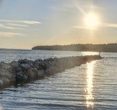 Pietre bagnate, ciottoli sulla riva di mare con acqua frizzante intorno e riflessione dei raggi del sole sulle onde di acqua Cana fotografia stock libera da diritti