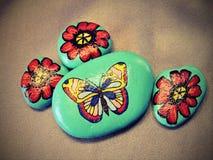 Pietre con la farfalla ed i fiori dipinti Fotografia Stock Libera da Diritti