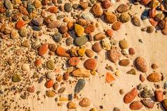 Pietre dei ciottoli su una spiaggia sabbiosa Fotografia Stock