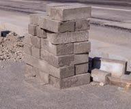 Pietre della pavimentazione impilate vicino alla strada costruzione, industriale immagine stock libera da diritti
