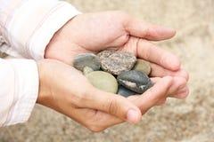 Pietre della spiaggia in mani del `s dell'uomo Fotografia Stock Libera da Diritti