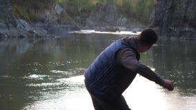 Pietre di lancio del giovane nel fiume della montagna Fotografie Stock