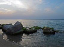 Pietre di Mossed nel mare con il cielo di tramonto fotografie stock