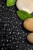 Pietre di zen sul nero con le gocce di acqua Immagini Stock Libere da Diritti