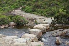 Pietre facenti un passo enormi attraverso una corrente scorrente vicino agli stagni del fatato sull'isola di Skye Fotografia Stock