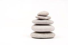 Pietre grige equilibrate sopra fondo bianco Fotografia Stock