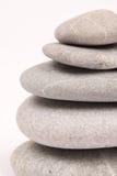Pietre grige equilibrate sopra fondo bianco Immagini Stock