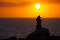 Pietre impilate per un desiderio sul tramonto Mediterraneo Fotografie Stock