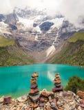 Pietre impilate sul lago Humantay nel Perù fotografia stock