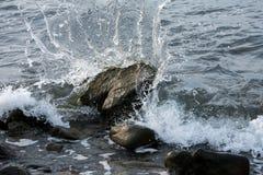 Pietre infuriantesi della spuma dell'acqua di mare fotografia stock