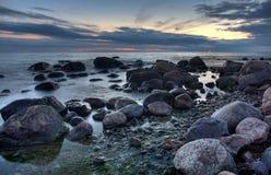 Pietre nel mare dopo il tramonto Fotografia Stock