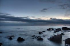 Pietre nel mare dopo il tramonto Immagine Stock