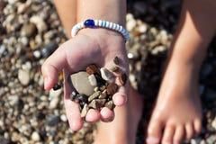 Pietre nella mano del ragazzino che si siede sulla spiaggia Fotografia Stock