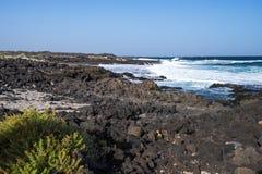 Pietre nere del vulcano e sabbia bianca sulla linea costiera immagini stock libere da diritti