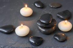 Pietre nere e candele brucianti su fondo scuro Immagini Stock