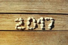 2017 pietre presentate su un pilastro di legno del fondo Fotografia Stock