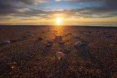 Pietre rotonde sulla spiaggia sabbiosa sul fondo di tramonto Fotografie Stock