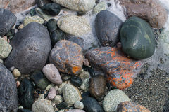 Pietre a strisce variopinte bagnate ed arrotondate dalle onde Immagini Stock