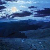 Pietre sul pendio di collina di catena montuosa alla luce di luna piena Fotografia Stock