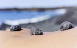 Pietre sul retro di un uomo sulla spiaggia Fotografia Stock