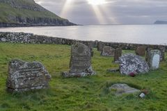 Pietre tombali al cimitero alla chiesa di Kirkjubø con i raggi del sole o della luce di Dio, Kirkjubøur, isole faroe Fotografia Stock