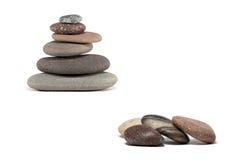 Pietre variopinte e cairn di pietra isolati su bianco Immagini Stock