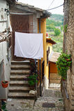PIETRELCINA, ITALY - SEPTEMBER, 29: Small street of Pietrelcina with white cat and linen, September 29, 2012 Stock Photography