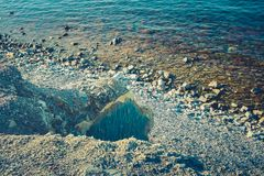 Pietroso fantastico, tonificato in blu, spiaggia con una spuma calma immagini stock libere da diritti