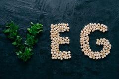 Pietruszka i suchy garbanzo w formie listy znaczy veg, jarosz odizolowywający nad ciemnym tłem Organicznie proteinowy produkt weg obraz stock