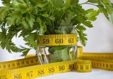 Pietruszka, zielenie w szkle obok pomiarowej taśmy Zdjęcia Stock