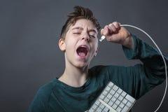 Śpiewacki nastoletni chłopak z komputerową klawiaturą Zdjęcia Royalty Free