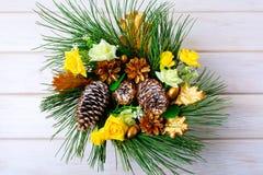 Pieza central de la tabla de la Navidad o guirnalda de la puerta con los conos de oro Foto de archivo libre de regalías