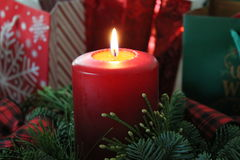 Pieza central de la vela que brilla intensamente con los regalos Foto de archivo