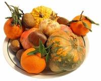 Pieza central del otoño con las castañas de las calabazas y las naranjas maduras Imagen de archivo libre de regalías