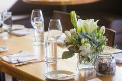 Pieza central floral en una tabla en una cena Foto de archivo libre de regalías