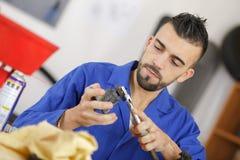 Pieza de automóvil de limpieza del mecánico en taller imagen de archivo libre de regalías