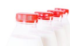Pieza de cuatro botellas de leche con el casquillo rojo Foto de archivo libre de regalías