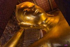 Pieza de la cara de la estatua de Buda del oro en templo real del pho del wat en Tailandia foto de archivo