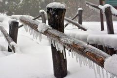 Pieza de la cerca de madera congelada en la nieve fotografía de archivo