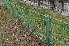 Pieza de la cerca verde decorativa del hierro en la hierba en el parque Fotografía de archivo libre de regalías