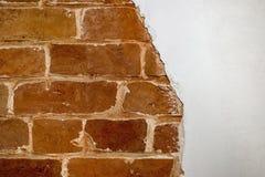 Pieza de la pared de ladrillo roja de una casa vieja con un modelo figurado de la masilla blanca Fondo, textura que pone en contr fotografía de archivo libre de regalías