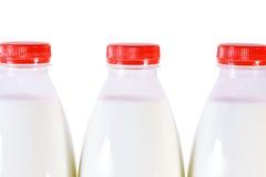 Pieza de tres botellas de leche con el casquillo aislado Fotografía de archivo