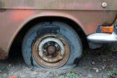 Pieza de un coche marrón viejo con un neumático desinflado gris en la arena imagen de archivo