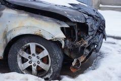 Pieza de un coche negro quemado en un desplome con un tope y una rueda en la nieve en la calle fotografía de archivo libre de regalías