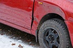 Pieza de un coche rojo con una abolladura en el ala y una rueda negra en el camino en la nieve foto de archivo