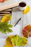 Pieza de un libro abierto, de un cuaderno con una pluma, de taza y de hojas de otoño Fotos de archivo