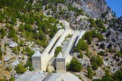 Pieza de una presa hidroeléctrica en un barranco verde Imágenes de archivo libres de regalías